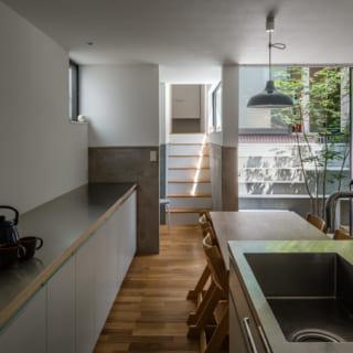 キッチン・ダイニング。キッチンはオリジナル。壁に沿ってつくったカップボードは家電などを置けるほか、食器収納にも使える。ここからも中庭の緑が見え、気持ちよく家事ができる。写真奥は中2階への階段
