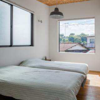 2階の主寝室。屋根の下の部屋はウッドチップの構造材を見せて天井とし、デザイン性とコストダウンを両立