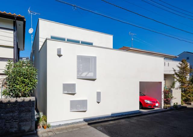 南の外観。通行人からは2階の室内が見えない高さの白塀で囲み、プライバシーを確保。一方で、白塀には出窓タイプの小窓を複数設け、表情のある佇まいに。小窓を覆う白いエキスパンドメタルは、斜めの角度をつけた。こうすると、中が見えにくくなる効果が高まる