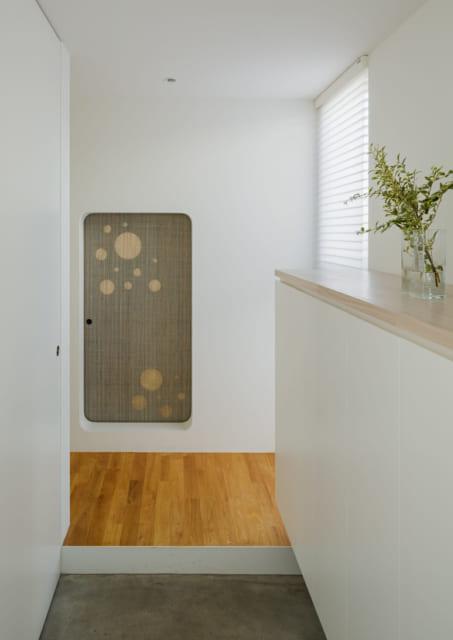 玄関を入ると和室への引き戸がある。木材を丸くくり抜いて麻を張った引き戸の透け感が空間の奥行きを生む
