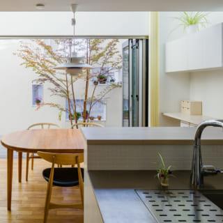 南向きのキッチンに立つと正面にテラスがあり、視線が抜ける。白塀の小窓部分は、植物などをディスプレーできる出窓タイプ。白い壁に小さな絵画を飾っているようにも見えて楽しく、「塀」の圧迫感はゼロ
