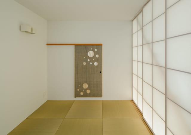 和室は、リビング・ダイニング側の障子を閉めると独立した空間になる。写真正面の引き戸は茶室の躙り口(にじりぐち)をイメージして小さめにつくった。青く塗装した木材に麻を張っているため独特の色彩に。日本画を飾っているかのようで、インテリアのポイントになっている
