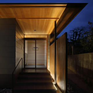 玄関の建具の欄間は透明なガラス製。可動部が横ルーバーとなっており、室内の柔らかな光が漏れる。玄関横の縦格子はライトアップされ、訪れる者を出迎えてくれる