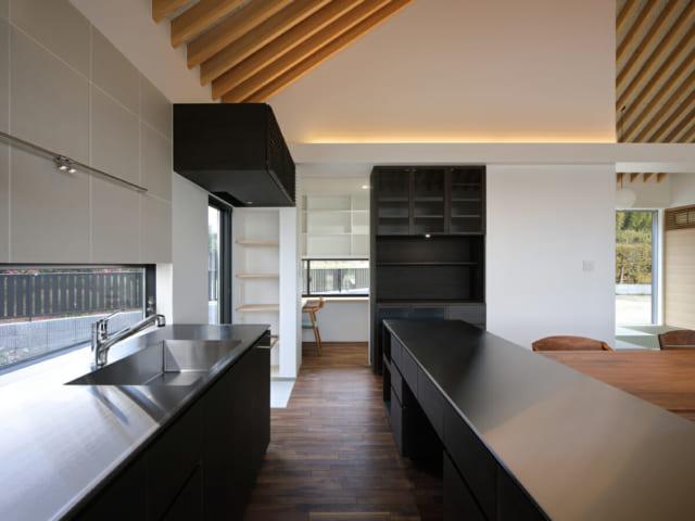 キッチンカウンター末端に、採光と通風のため横すべり出し窓を設置。食器棚、カウンター、エアコン収納の家具は、全て黒色塗装の造作家具で統一感を演出