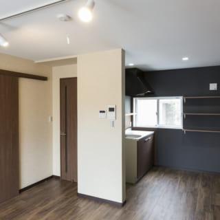 101号室。シックな木目やアクセントクロスでカフェ風の空間をイメージ。料理好きな女の子の入居を想定し、キッチンは独立したレイアウトに。どの部屋も洒落た内装だが床はフローリング風の塩ビタイルを用い、デザイン性とメンテナンスの利便性を両立している