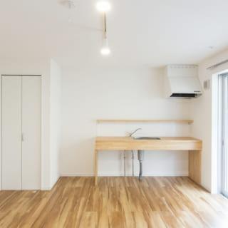102号室の東面。オリジナルのキッチンはオープンな造りで、友達を呼んでワイワイ料理や食事を楽しめる空間になっている。左の壁のドアの先は玄関。どの部屋も、玄関を開けてワンクッション置いてから住空間が広がるように設計している