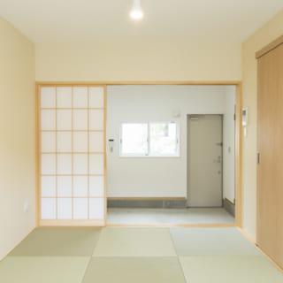 105号室。琉球畳の洒落た和室で床座の生活ができる。右奥の玄関ドアを開けるとほかの学生さんも通る中庭なので、広い土間をつくって中庭と住空間の距離を確保した