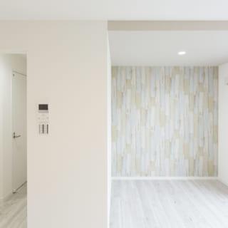202号室の東面。左側は玄関ホールで右側が住空間。間には造り付けの収納があり、玄関を開けてもすぐに中が見えない安心感がある。アクセントクロスは古い木材にペンキを塗ったようなデザインで、アンティーク調の木目の床と好相性