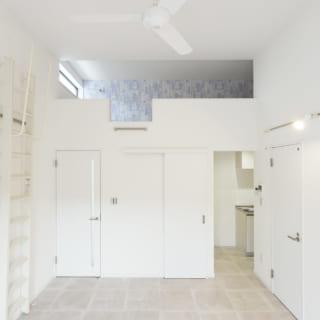203号室。天井を高く取り、ロフトを設置。ビルを描いた青いクロスや白いシーリングファンが爽やかな印象