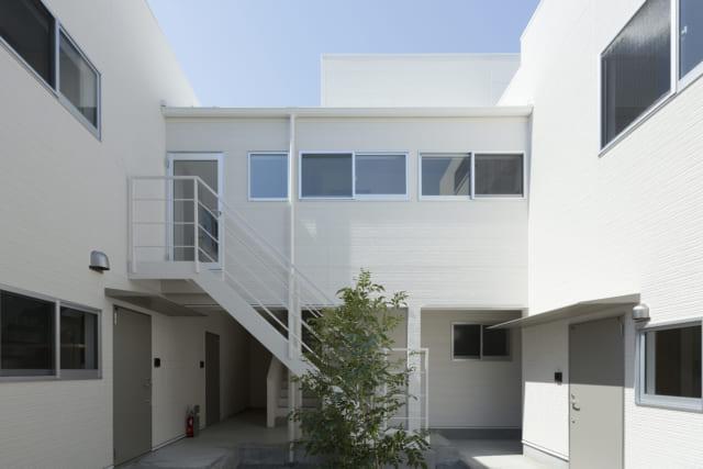 共用エントランスから先へ進むとシンボルツリーのある中庭に出る。1階の部屋の玄関はいずれも中庭に面しており、毎日必ず緑を眺める心地よい暮らしがかなう。白い非常階段の奥には2階への内階段があり、2階に住む学生さんも中庭を見てから出入りできる