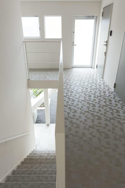 2階への内階段や、2階の共用廊下にも明るい陽光が入る。床にはタイル風のシートを張って高級感を演出