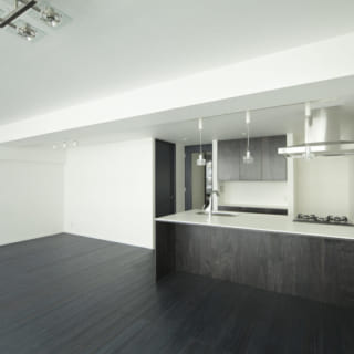 ダイニング側から見たLDK。造作家具や建具、キッチンの木製部分は床と同じ素材を使っており、インテリアに統一感が生まれている。オリジナルのキッチンは一般的なサイズよりも天板の奥行きを深く取った。ダイニングとの距離が近く、食後に食器を下げるときもラクラク