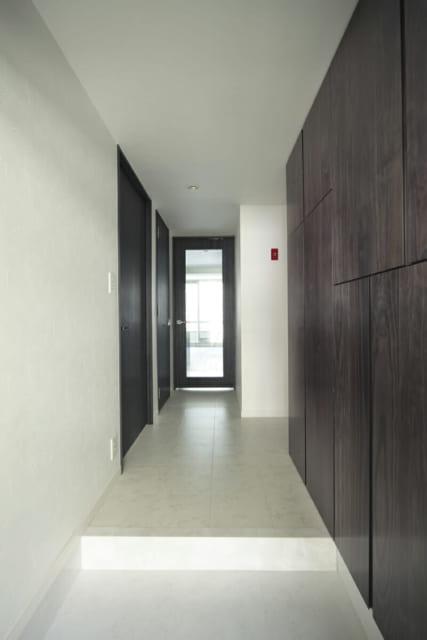 玄関を入った右側が収納と水まわり、左側が寝室・トイレ。奥のLDKのドアはガラス戸で、廊下にも光が入る
