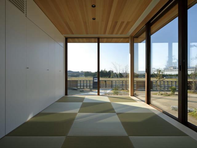 琉球畳が美しい和室。壁面には凹凸のない作り付けの収納。サッシの枠は天井と床下に埋め込み、スッキリとした空間にしている