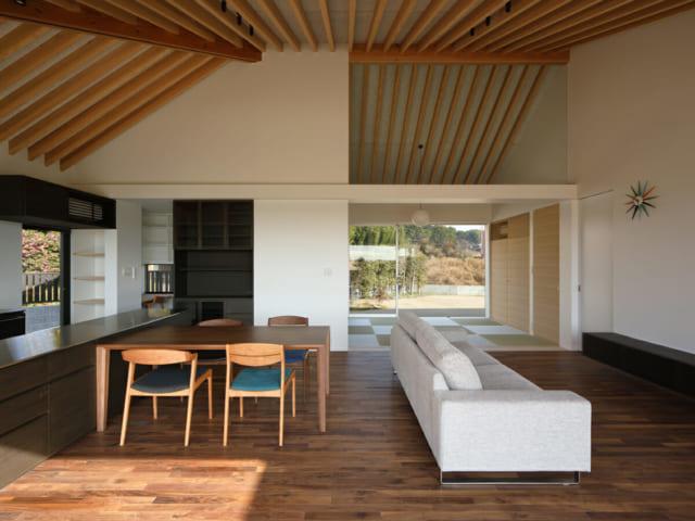 リビングと座敷の天井は、勾配屋根の垂木現し。座敷の仕切り上部をガラスにすることで、天井の一体感を生み、垂直方向にもおおらかな開放感を実現した。座敷奥の窓を広くすることで、南北の風通しと抜け感を実現