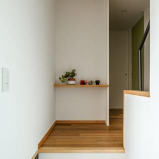 土地に段差があるため、玄関を入ったら数段の階段をのぼって家の中に入る。正面には小さなディスプレー棚