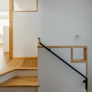 2階キッチンの仕切り壁、階段の手すり壁の2カ所に小窓を設置。2つの小窓が呼応する建築デザインが楽しい