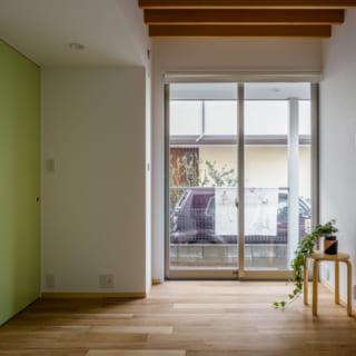 1階寝室。「コンパクトだからこそ、味気なくならないように」と、天井の一部は構造材を現し(あらわし)にして変化をつけた。写真左の出入口の引き戸もグリーン系の明るいカラーで塗装。ホッとなごめて、愛着の湧く空間になっている