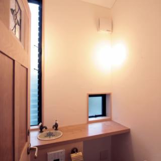 2階トイレ。人目を気にせずにすむ方角に窓があり、屋外の緑を眺められる。木製のカウンターは水に強い栗材