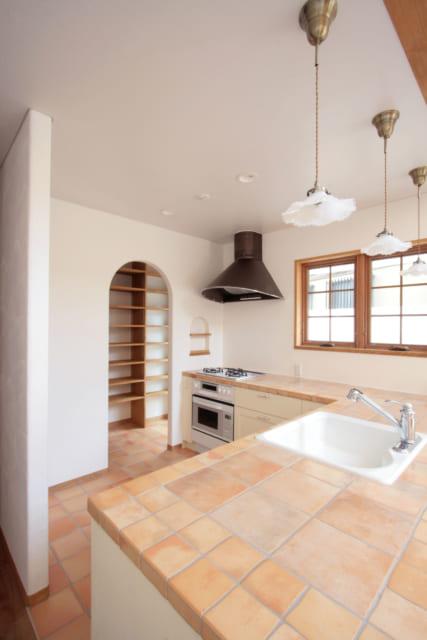 キッチンの床はテラコッタタイル、カウンター天板は磁器系タイル。奥にはパントリー収納と勝手口がある