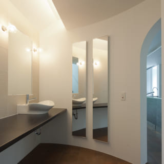 奥様の要望で2階に設けられたパウダールーム兼ご主人の書斎。壁にかけられている鏡の奥は収納になっており、間接照明で空間を彩る