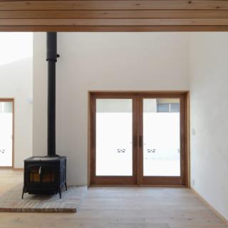 リビングスペース。内装はカントリー調で、壁はスイス漆喰、床は無垢のバーチ材(カバザクラ)、天井はウエスタンレッドシダー材、木製窓枠はマーヴィン社製と、自然素材を贅沢に使用。薪ストーブが温かみを醸す空間は、本物志向の素材ならではの上質感にあふれている