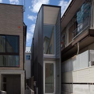 土間のギャラリーを設けたことで、この土間が幅1.5mの家の顔に。普通の玄関だと寂しいため、外観にガラスと金属板を多用して、あえて住宅に見えないようにした