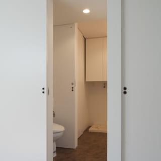 1階のトイレ。両サイドにスライディングドアが設けられて、洗面室からとお母様の居室からの両方から入れるように工夫されており、フルハイトのサイズで閉めた時には壁の一部となるように設えられている