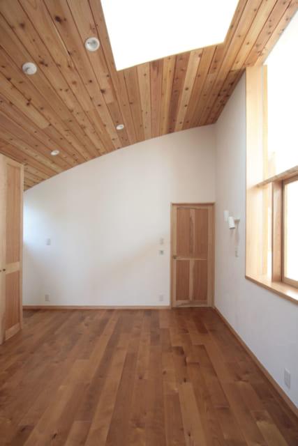 アーチ屋根の曲線がよくわかる2階主寝室もトップライト付き。木製の扉やクロゼットも床材と同じバーチ材