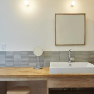 木材とグレーのタイルのコントラストが美しい洗面台。この左側には洗濯機置き場が設けられている