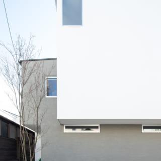 西の道路から見たM邸。白×温かみのあるグレーで街並みに溶け込む外観。道路側には駐車場スペースもある