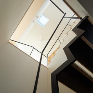 1階の階段から上を見上げると、3階天井のトップライトが見える。ここから入る光で玄関も明るい