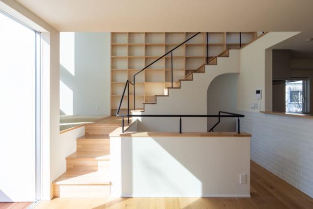 2階のリビング・ダイニングは、本棚のある階段との一体感も十分。階段は座り心地もよく、住空間として活躍する。手前の階段を数段のぼった左手は畳スペース。リビング・ダイニングより少し高くしたことで空間の立体的な広がりが生まれ、ほどよい距離感の居場所になった