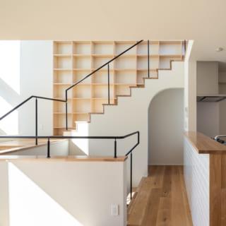 奥のアーチの先はワークスペース。その手前に1~2階の階段がある。2階に上がるとワークスペースが視界に入り、LDKを通って畳スペースの横も通り過ぎると、本棚のある階段で3階へ行ける。階段をのぼる際にさまざまな居場所を通過する動線が、家族のコミュニケーションを生む