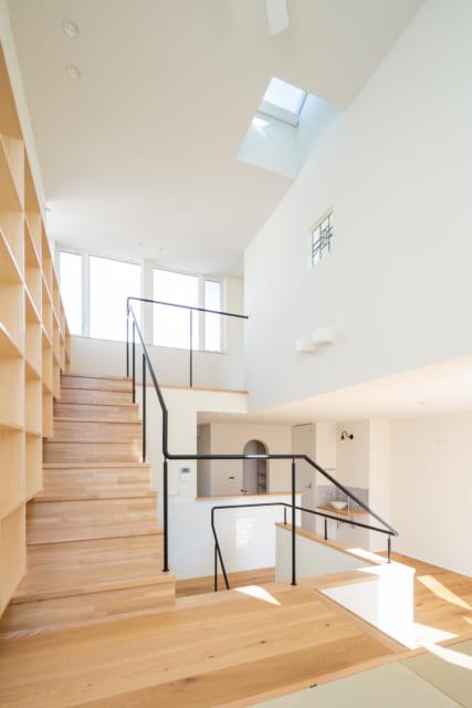 畳スペースからの眺め。LDKも3階への階段も見渡せる。ステンドグラスが入った右の白壁は3階の子ども室