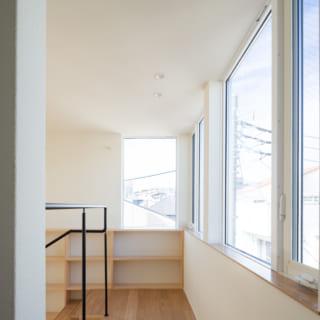3階通路。写真右、安定した光が入る北側に連続のハイサイド窓を設置。吹抜けを介して階下にも光が入る