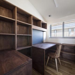 デスクと壁一面の本棚を備えた2階の書斎スペース。手作り感のある造作家具が温かい雰囲気を醸し出している