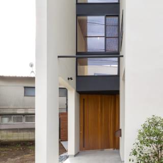 アプローチの奥のエントランス。大きな引き戸の向こうには開放的な土間の玄関とセカンドリビングが配されている