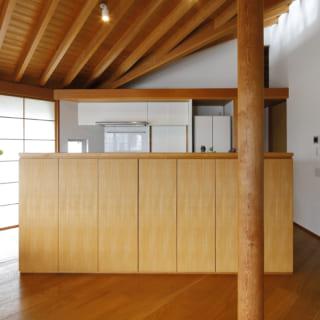 リビング脇のアイランドキッチンは、内装と統一感のあるオリジナル製。キッチン奥には、寝室などのプライベートスペースが広がる