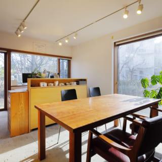 1階エントランス横にある事務所スペース。大きくとられた2つの窓からは庭の景色が眺められ、四季の移ろいを感じながら仕事ができる