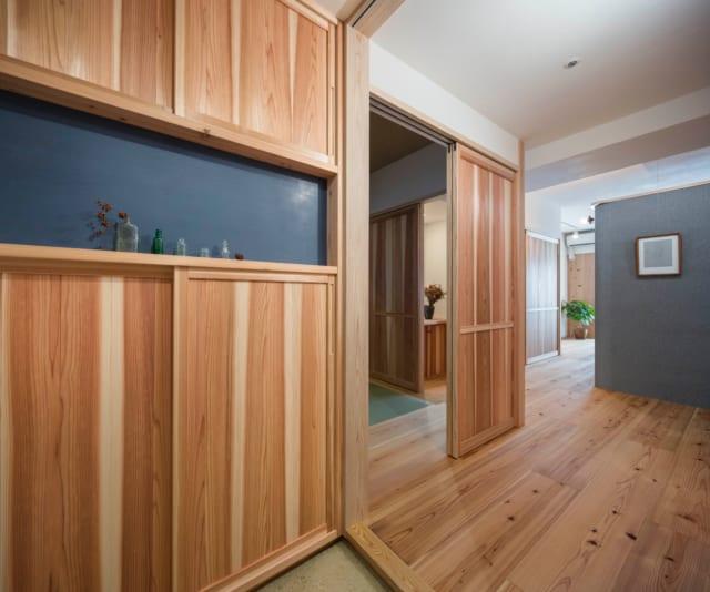 玄関と居室の境の引き戸を開けると、左手に和室、奥にLDKがある。写真左手前のシューズクローゼットも徳島の杉板。好きなものを飾ることができるニッチ棚の壁は、土壁に光沢を出す大津磨きの技法を用いている。藤田さんと懇意にしている若い左官職人の手によるもの