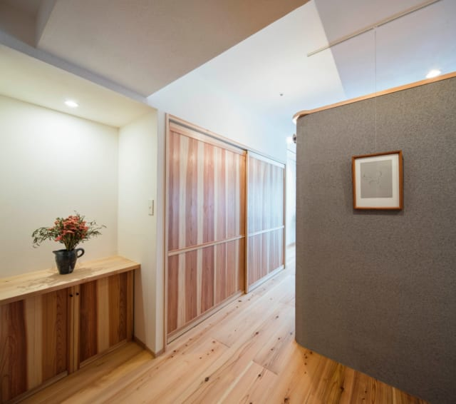 ブルーグレーの壁は書斎の壁。その左脇にはクローゼットがある。クローゼットや、その手前の収納棚の扉に用いた杉は、木の赤い部分と白い部分が混じった「源平」という杉板で、かつ、節の少ないもの。時間が経つと赤と白が均一に馴染み、味わい深い色になる