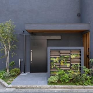 西面にある玄関へのアプローチ。右の玄関ドアはバルコニーの軒天と同じピーラー(ベイマツ材の一種)で、年輪幅が細く均一にそろった木目が高級感を醸す。ルーバーの植栽壁は緑の彩りを添えるとともに、夏場に涼しい空気を送る効果もある