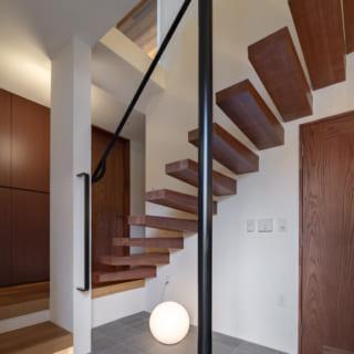 1~2階の階段は、宙に浮いたような片持ち階段。本来、木造住宅では難しいが鉄骨の支えを入れて実現した