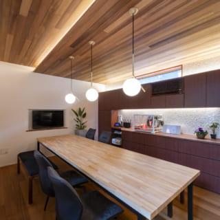 ダイニングは木板天井の間接照明や、マイケル・アナスタシアデスのペンダントライトで華やかな雰囲気に