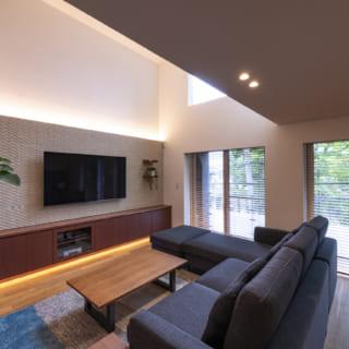 リビングのテレビ背後は漆喰壁とタイルの透かし壁の2層になっており、間接照明の柔らかな光がくつろぎの時間を演出。空間の広がりを感じさせる効果もある