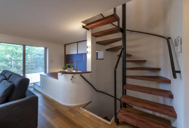 インテリアのアクセントになっている2~3階へのらせん階段。写真中央は下に向かう階段の入口。この階段の先には、大人がちょっとしゃがんで入る高さの広い床下収納がある。天井を低めにした1階ガレージと、2階リビングの間を有効活用したものだ