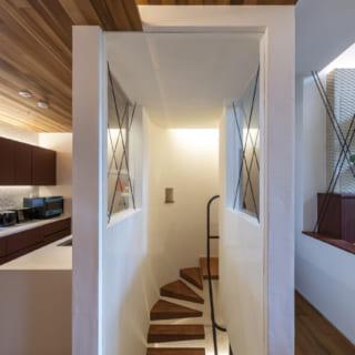 1~2階への片持ち階段。西の外壁の曲線に沿った三角形の踏み板も美しく、眺めて楽しいアートのよう