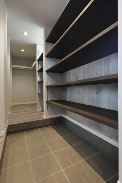 土間の床から天井までたっぷりと収納できる可動棚。玄関の奥にはファミリークローゼットも配置