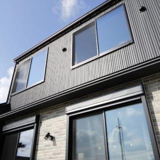 黒のガルバリウム外壁とレンガ調サイディングのツートンで、ブルックリン・テイストをイメージした外観デザイン